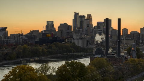 DXP001_000436 - Aerial stock photo of The downtown skyline at sunset, seen from smoke stacks by the river, Downtown Minneapolis, Minnesota