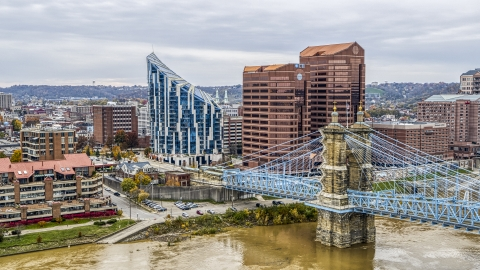 DXP001_000466 - Aerial stock photo of Condo complex and two office buildings behind the Roebling Bridge spanning Ohio River in Covington, Kentucky