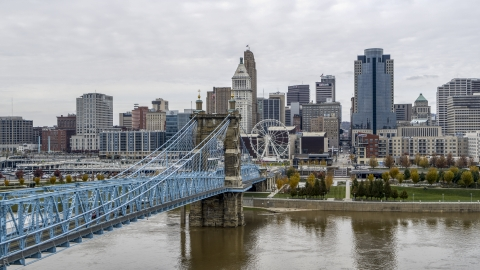 DXP001_000472 - Aerial stock photo of The side of the Roebling Bridge with the Ferris wheel and skyline in the distance, Downtown Cincinnati, Ohio
