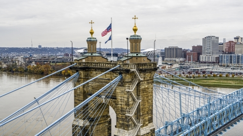 DXP001_000473 - Aerial stock photo of Flag on top of the Roebling Bridge spanning the Ohio River, Downtown Cincinnati, Ohio