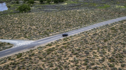 DXP001_007_0002 - Aerial stock photo of A black SUV parked on a desert road in Carson City, Nevada
