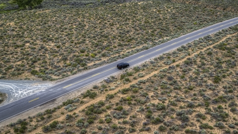 DXP001_007_0003 - Aerial stock photo of A black SUV parked on the side of a desert road in Carson City, Nevada