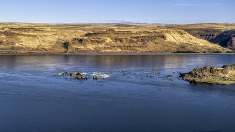DXP001_019_0014 - Aerial stock photo of Small rock formations in the Columbia River in Goldendale, Washington