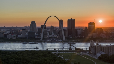 DXP001_029_0005 - Aerial stock photo of The setting sun behind the Gateway Arch and Downtown St. Louis, Missouri