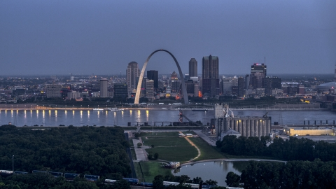 DXP001_037_0001 - Aerial stock photo of The Gateway Arch at twilight, visible from across the Mississippi River, Downtown St. Louis, Missouri
