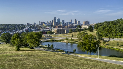 DXP001_045_0006 - Aerial stock photo of A view of the city's skyline from green grass beside a small lake in Kansas City, Missouri