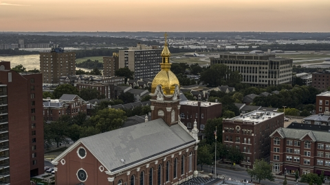 DXP001_051_0007 - Aerial stock photo of A brick cathedral with golden steeple at sunset in Downtown Kansas City, Missouri