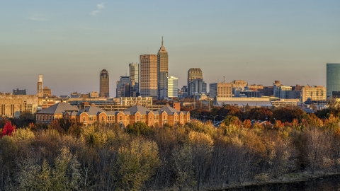 DXP001_092_0009 - Aerial stock photo of The city's skyline at sunset, seen from trees and apartment complex, Downtown Indianapolis, Indiana