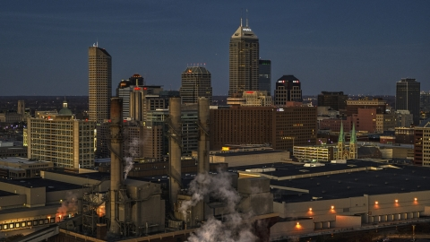 DXP001_093_0001 - Aerial stock photo of Smoke stacks and a view of city skyline at twilight in Downtown Indianapolis, Indiana