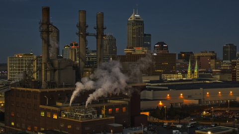 DXP001_093_0003 - Aerial stock photo of Factory smoke stacks with view of the city skyline at twilight, Downtown Indianapolis, Indiana