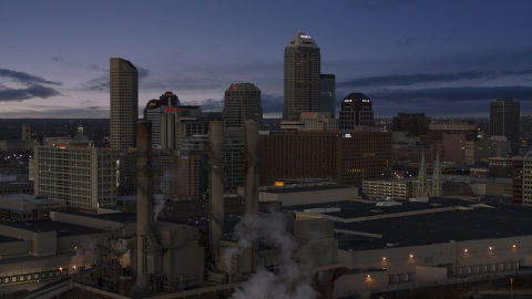 DXP001_093_001 - Aerial stock photo of Smoke stacks and a view of city skyline at twilight in Downtown Indianapolis, Indiana