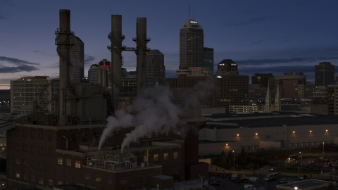 DXP001_093_003 - Aerial stock photo of Factory smoke stacks with city skyline in the background at twilight, Downtown Indianapolis, Indiana