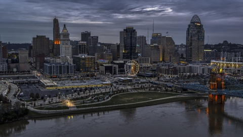 DXP001_097_0015 - Aerial stock photo of The city skyline and bridge lit at sunset, seen from Ohio River, Downtown Cincinnati, Ohio