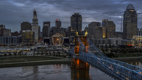 DXP001_097_0016 - Aerial stock photo of A view of the city skyline and Ferris wheel at sunset, seen from bridge and Ohio River, Downtown Cincinnati, Ohio