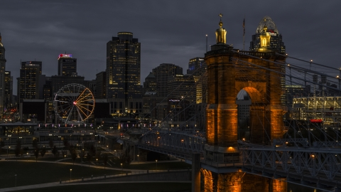DXP001_098_0008 - Aerial stock photo of City skyline, Ferris wheel and Roebling Bridge lit up at twilight, Downtown Cincinnati, Ohio