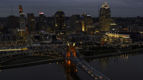 DXP001_098_0009 - Aerial stock photo of A view of the lights of city skyline and bridge at twilight, seen from river, Downtown Cincinnati, Ohio