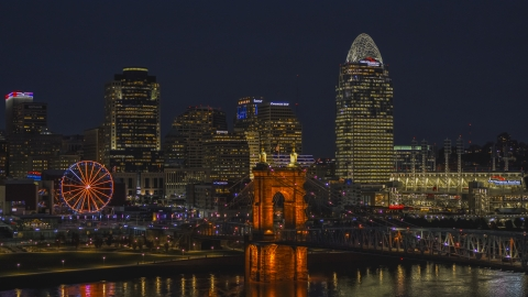 DXP001_098_0019 - Aerial stock photo of The bridge, tall skyscrapers and Ferris wheel at night in Downtown Cincinnati, Ohio
