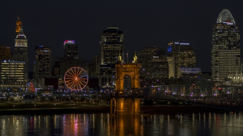 DXP001_098_0022 - Aerial stock photo of Ferris wheel, Roebling Bridge and city skyline at night, Downtown Cincinnati, Ohio