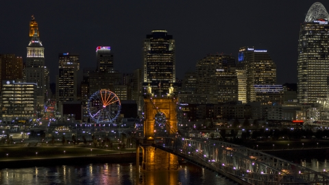 DXP001_098_0023 - Aerial stock photo of The Ferris wheel by Roebling Bridge at night, with city skyline in background, Downtown Cincinnati, Ohio