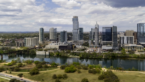 DXP002_102_0014 - Aerial stock photo of Tall city skyscrapers across Lady Bird Lake, Downtown Austin, Texas