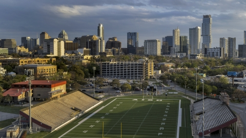 DXP002_105_0002 - Aerial stock photo of A view of skyscrapers and office buildings at sunset in Downtown Austin, Texas, seen from football stadium