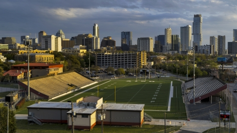 DXP002_105_0003 - Aerial stock photo of A view of skyscrapers from a football field at sunset in Downtown Austin, Texas