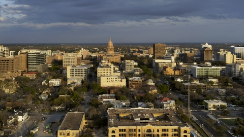 DXP002_105_0005 - Aerial stock photo of The Texas State Capitol dome and office buildings at sunset before descent in Downtown Austin, Texas