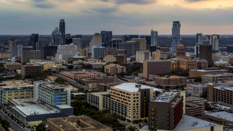 DXP002_105_0011 - Aerial stock photo of A hospital, with skyscrapers and capitol dome in distance at sunset in Downtown Austin, Texas