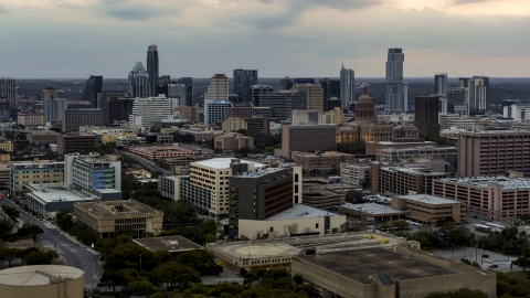 DXP002_105_0012 - Aerial stock photo of Hospital complex, office buildings and capitol dome at sunset, skyscrapers in distance in Downtown Austin, Texas