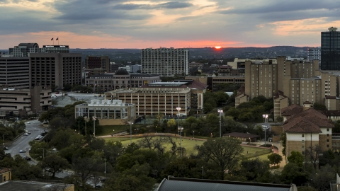 DXP002_105_0013 - Aerial stock photo of The setting sun in the distance while flying near the university, Austin, Texas