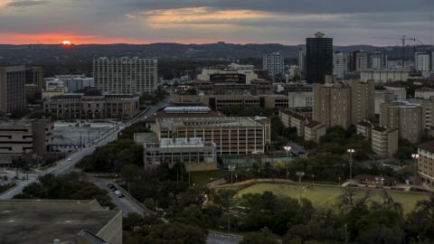 DXP002_105_0015 - Aerial stock photo of A view of the university campus with setting sun in distance, Austin, Texas