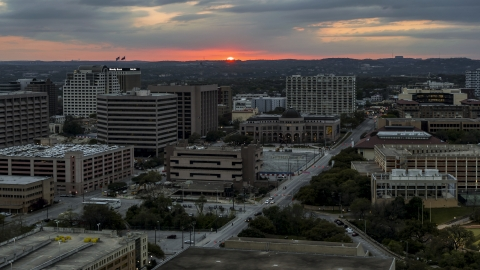 DXP002_105_0016 - Aerial stock photo of A view of distant, setting sun behind the university campus, Austin, Texas