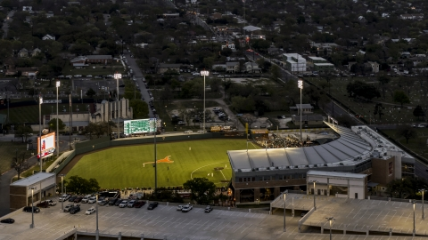 DXP002_105_0018 - Aerial stock photo of A baseball game at a stadium at the University of Texas at twilight, Austin, Texas
