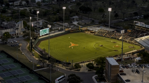 DXP002_105_0019 - Aerial stock photo of View of a baseball game at a stadium at the University of Texas at twilight, Austin, Texas