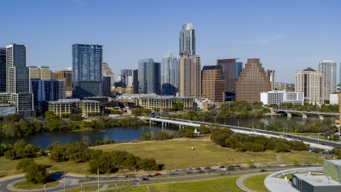 DXP002_109_0005 - Aerial stock photo of The city's skyline on the opposite side of Lady Bird Lake seen from a street near bridge, Downtown Austin, Texas