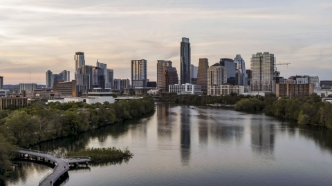 DXP002_110_0004 - Aerial stock photo of The city's skyline seen from low over Lady Bird Lake at sunset in Downtown Austin, Texas