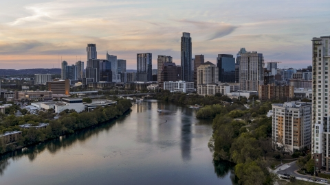 DXP002_110_0006 - Aerial stock photo of The waterfront skyline by Lady Bird Lake at sunset in Downtown Austin, Texas