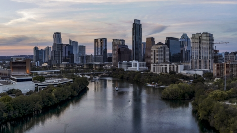 DXP002_110_0007 - Aerial stock photo of City skyline by Lady Bird Lake at twilight in Downtown Austin, Texas