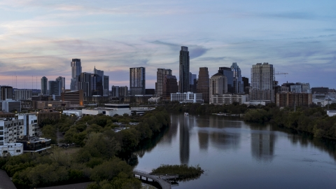 DXP002_110_0011 - Aerial stock photo of The city's waterfront skyline seen from low over Lady Bird Lake at twilight in Downtown Austin, Texas