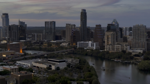 DXP002_110_0016 - Aerial stock photo of Focus on skyline by Lady Bird Lake and bridge at twilight in Downtown Austin, Texas