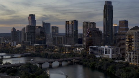 DXP002_110_0017 - Aerial stock photo of A bridge and skyscrapers beside Lady Bird Lake at twilight in Downtown Austin, Texas