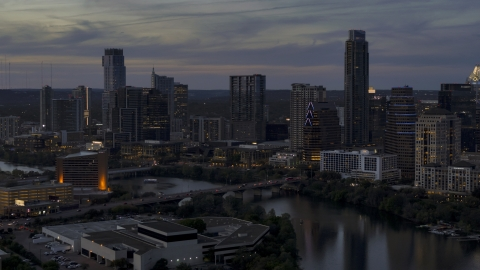 DXP002_110_0018 - Aerial stock photo of the waterfront skyline by Lady Bird Lake and bridge at twilight in Downtown Austin, Texas