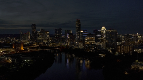 DXP002_111_0005 - Aerial stock photo of The waterfront skyline on the opposite shore of Lady Bird Lake at night in Downtown Austin, Texas