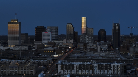 DXP002_115_0008 - Aerial stock photo of Towering skyscrapers reflecting light in the city skyline at twilight before descent, Downtown Nashville, Tennessee