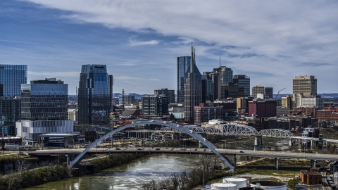 DXP002_116_0011 - Aerial stock photo of A river and bridge, skyscrapers in the background in Downtown Nashville, Tennessee