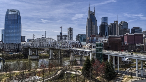 DXP002_117_0008 - Aerial stock photo of A pedestrian bridge with view of Broadway across the Cumberland River, Downtown Nashville, Tennessee
