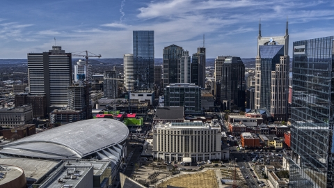 DXP002_117_0012 - Aerial stock photo of City's skyline behind the arena and hotel, Downtown Nashville, Tennessee