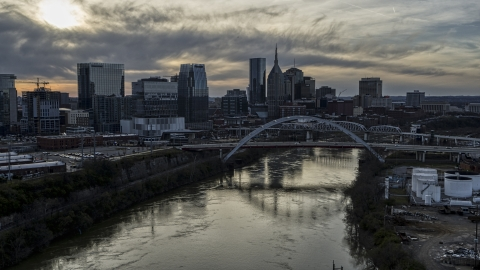 DXP002_119_0009 - Aerial stock photo of The city skyline behind a bridge on Cumberland River at sunset, Downtown Nashville, Tennessee