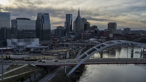 DXP002_119_0014 - Aerial stock photo of Bridge on Cumberland River at sunset, skyline behind it, Downtown Nashville, Tennessee