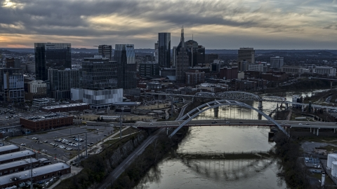 DXP002_119_0015 - Aerial stock photo of The skyline and a bridge over the Cumberland River at sunset, Downtown Nashville, Tennessee